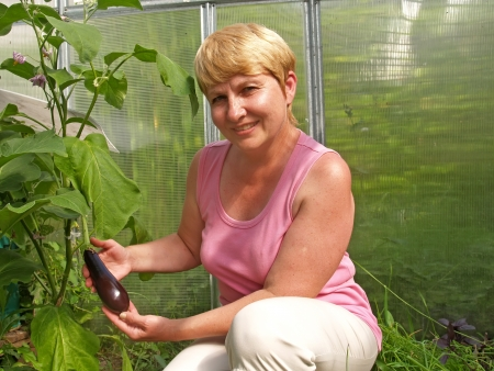 The woman holds an eggplant photo
