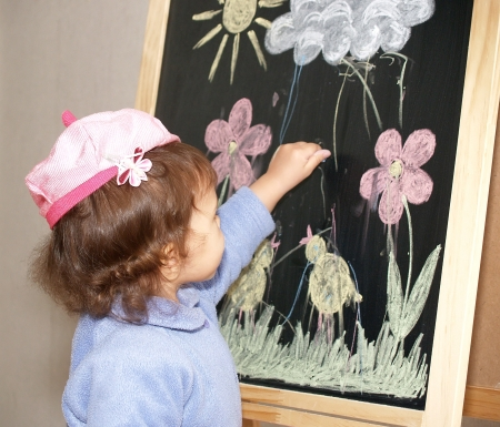 The little girl draws color pieces of chalk on an easel