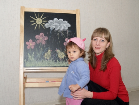 Mother teaches the small daughter to draw color pieces of chalk on an easel photo