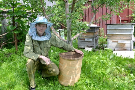 The young beekeeper from swarms to it on an apiary photo