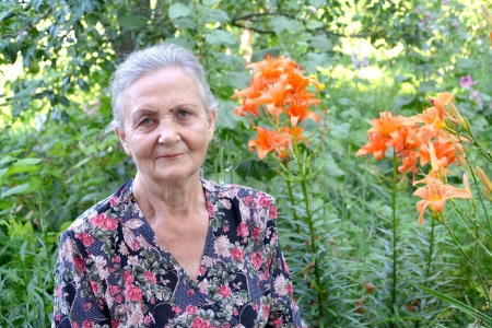 75 80: Portrait of the elderly woman in a garden Stock Photo