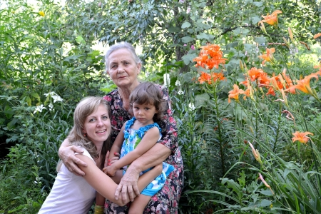 70 75 years: Family portrait in a garden, three generations