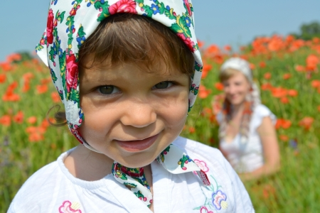 Portrait of the little girl in a colorful kerchief against red poppies photo
