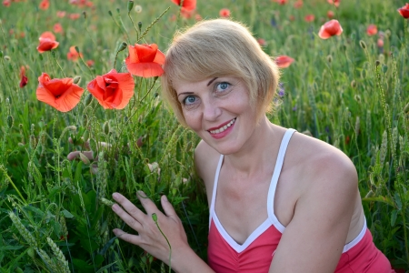 Portrait of the woman of average years with red poppies photo