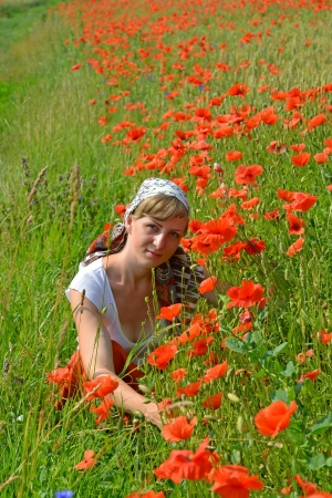 The young woman among red poppies photo