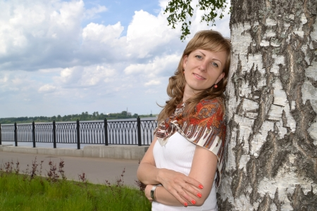 Portrait of the young woman who has leaned against a birch photo