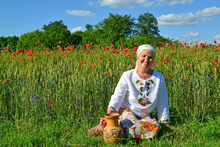 55 years old: The rural woman sits with a jug in a poppy field
