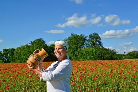 satisfies: The rural woman drinks water from a jug in a poppy field