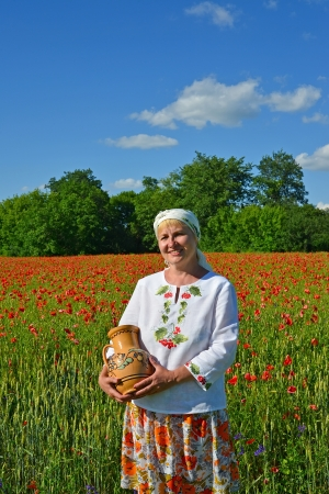 The rural woman costs with a jug in a poppy field photo