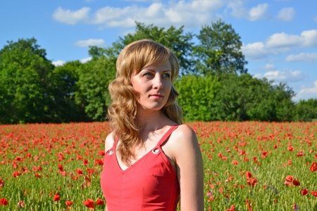 Portrait of the young woman in a poppy field photo