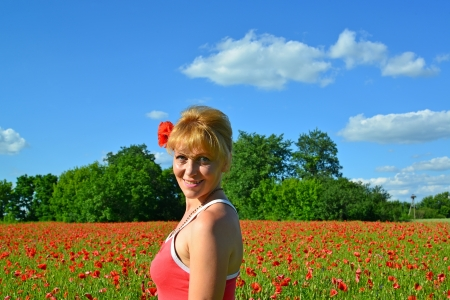Portrait of the woman with red poppy in hair photo