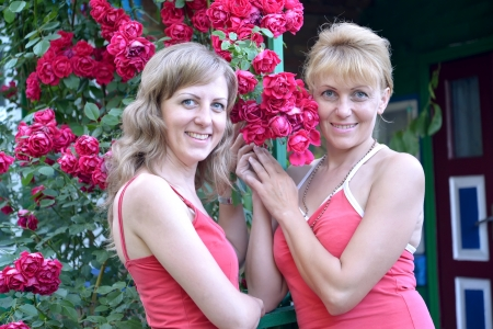 Two young women with red roses photo