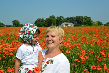 The grandmother and the granddaughter laugh in a poppy field photo