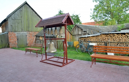 figurative: Figurative folding belfry with church bells in a yard of the rural house, Russia