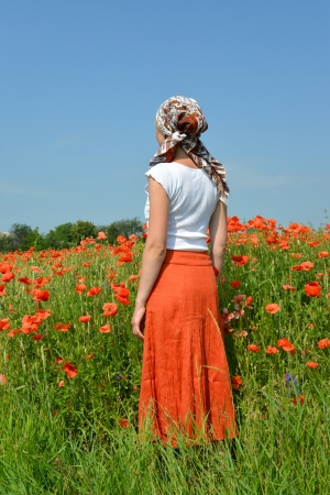 The young woman costs in a poppy field photo