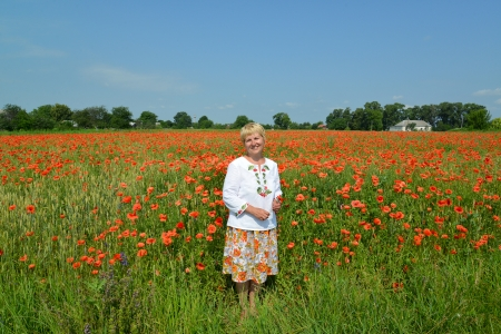 age 50 55 years: The rural woman costs in a poppy field
