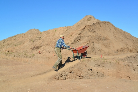 unskilled worker: The man of average years is lucky a wheelbarrow with soil on road construction