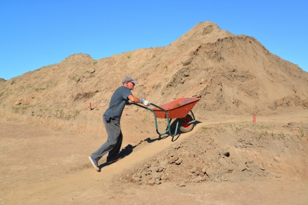 50 to 55 years old: The elderly worker is lucky a wheelbarrow with soil on road construction