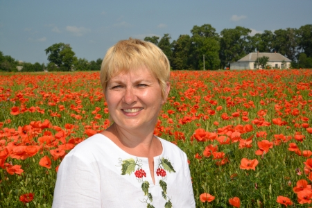 age 50 55 years: Portrait of the rural woman against a poppy field