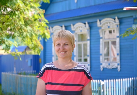 Portrait of the woman of average years against the blue wooden house  photo
