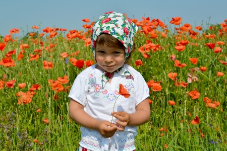 The little girl keeps red poppy in a poppy field photo