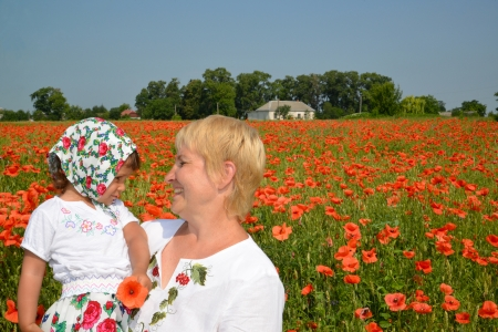 The grandmother and the granddaughter look at each other in the middle of a poppy field photo