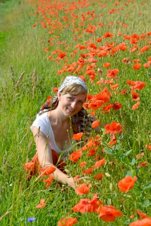The young woman sits on a grass among red poppies photo