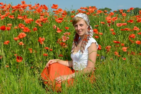 The young woman sits on a grass in a poppy field photo