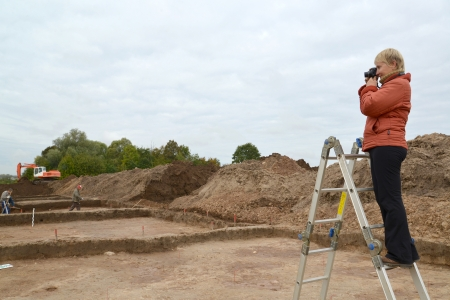 The woman photographs archeological excavations, standing on a ladder Stock Photo