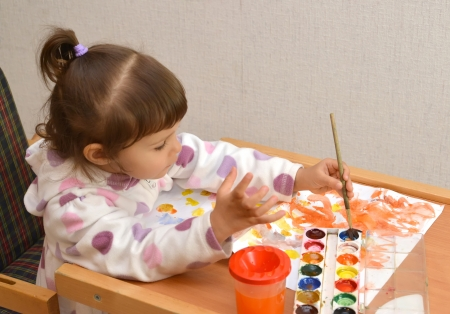 The little girl lefthander draws water color paints