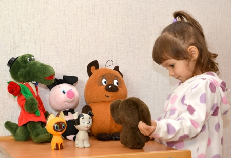 The little girl plays with the Cheburashka photo