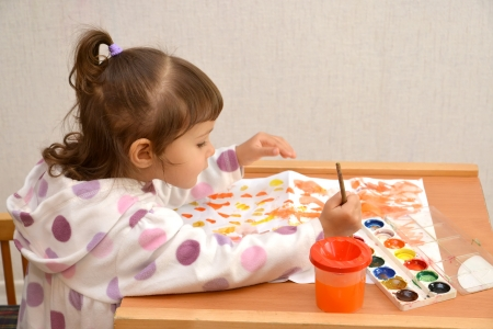 The little girl draws water color paints photo