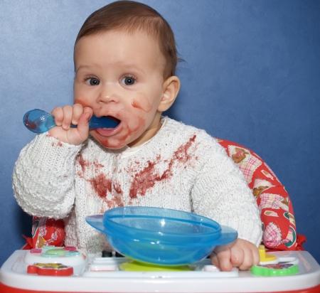 eat smeared baby: La ni�a come de forma independiente con una cuchara