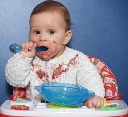 smeared hand: The little girl independently eats with a spoon  Stock Photo