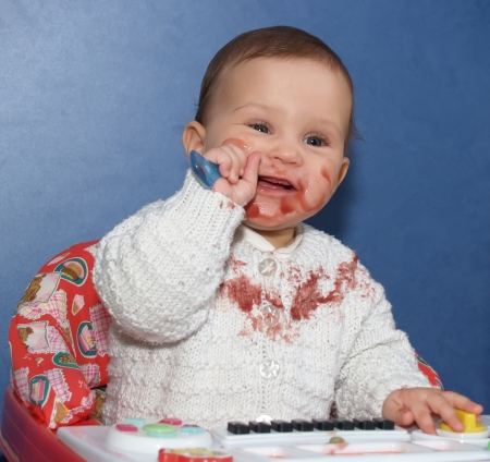 The little girl independently eats with a spoon Stock Photo - 24727100