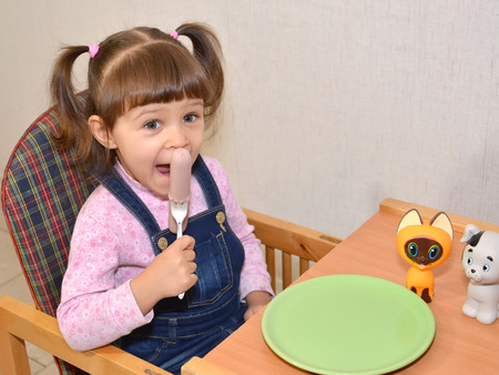 The little girl eats sausage by means of a fork photo