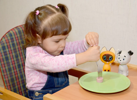 The little girl pins sausage on a fork photo
