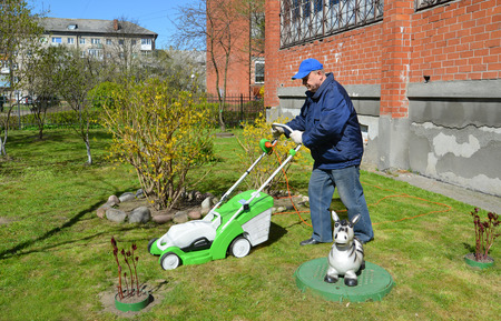The man cuts a grass a lawn-mower about the house