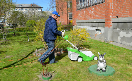 50 to 55 years old: The pensioner cuts a grass a lawn-mower about the house