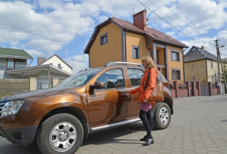 opens: The joyful woman opens a car door