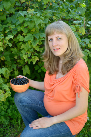 The pregnant woman with a bowl of black currant in a garden photo