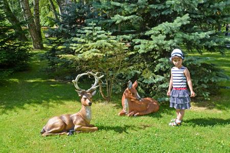 s horn: The little girl and garden sculptures of deer in a summer garden