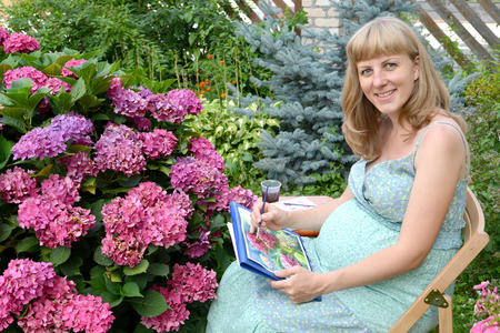 The young pregnant female artist draws water color paints a blossoming hydrangea in a garden Stock Photo