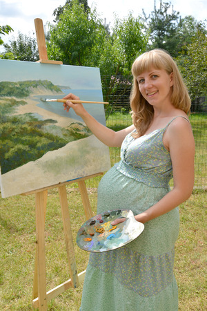 The young pregnant female artist draws a picture oil paints in the open air