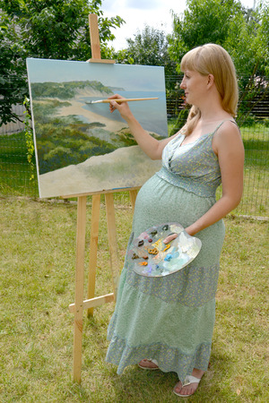 fair haired: The young pregnant female artist draws a picture oil paints in the open air