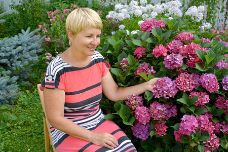 The joyful woman of average years has a rest in a garden near a blossoming hydrangea