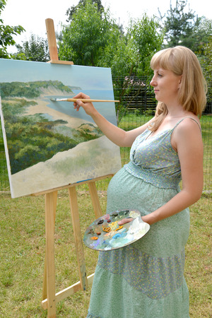 The young pregnant female artist writes a picture with oil paints Stock Photo