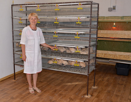 The woman in a white dressing gown stands near a cage with quails photo