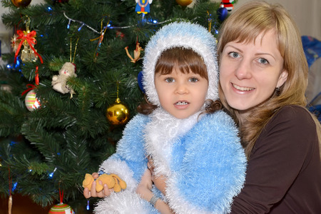 Portrait of the young woman with the child in the Snow Maidens suit near a New Year tree  photo