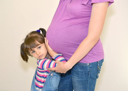 The little girl embraces hands a stomach of pregnant mother Stock Photo